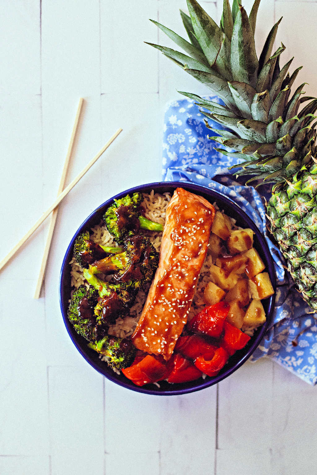 teriyaki salmon in a bowl with brown rice, roasted broccoli, red bell pepper, and pineapple on a wooden table with a whole pineapple and chopsticks
