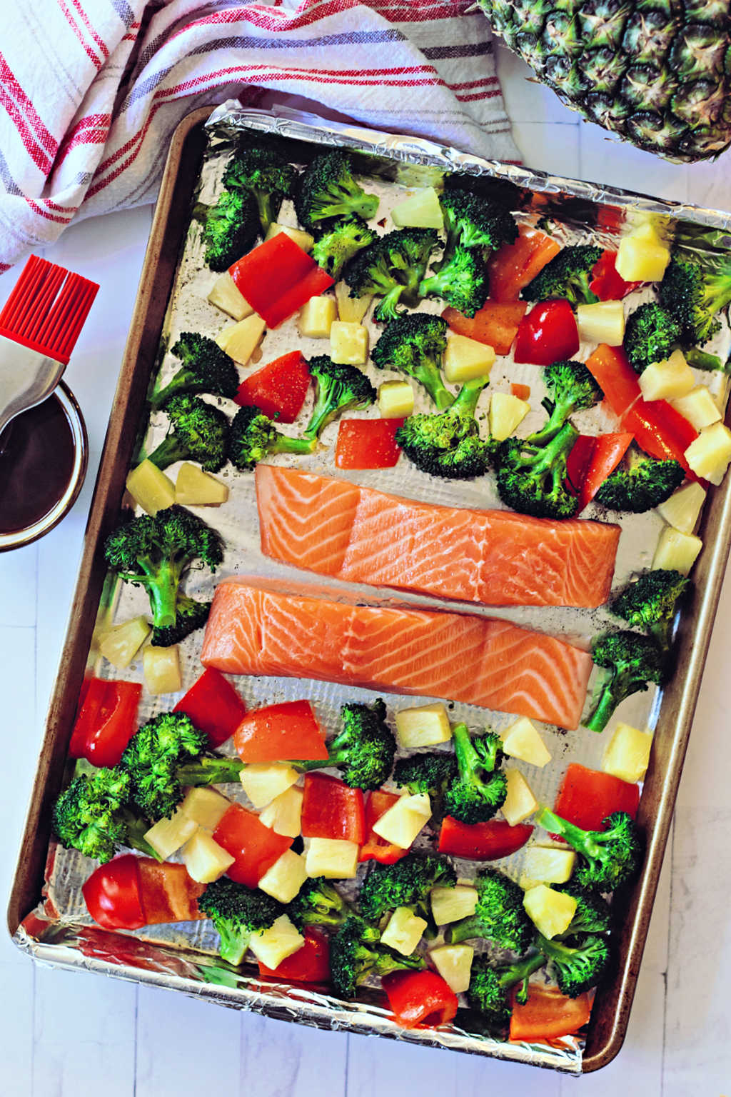 salmon filets, broccoli, red bell pepper, and pineapple on a sheet pan