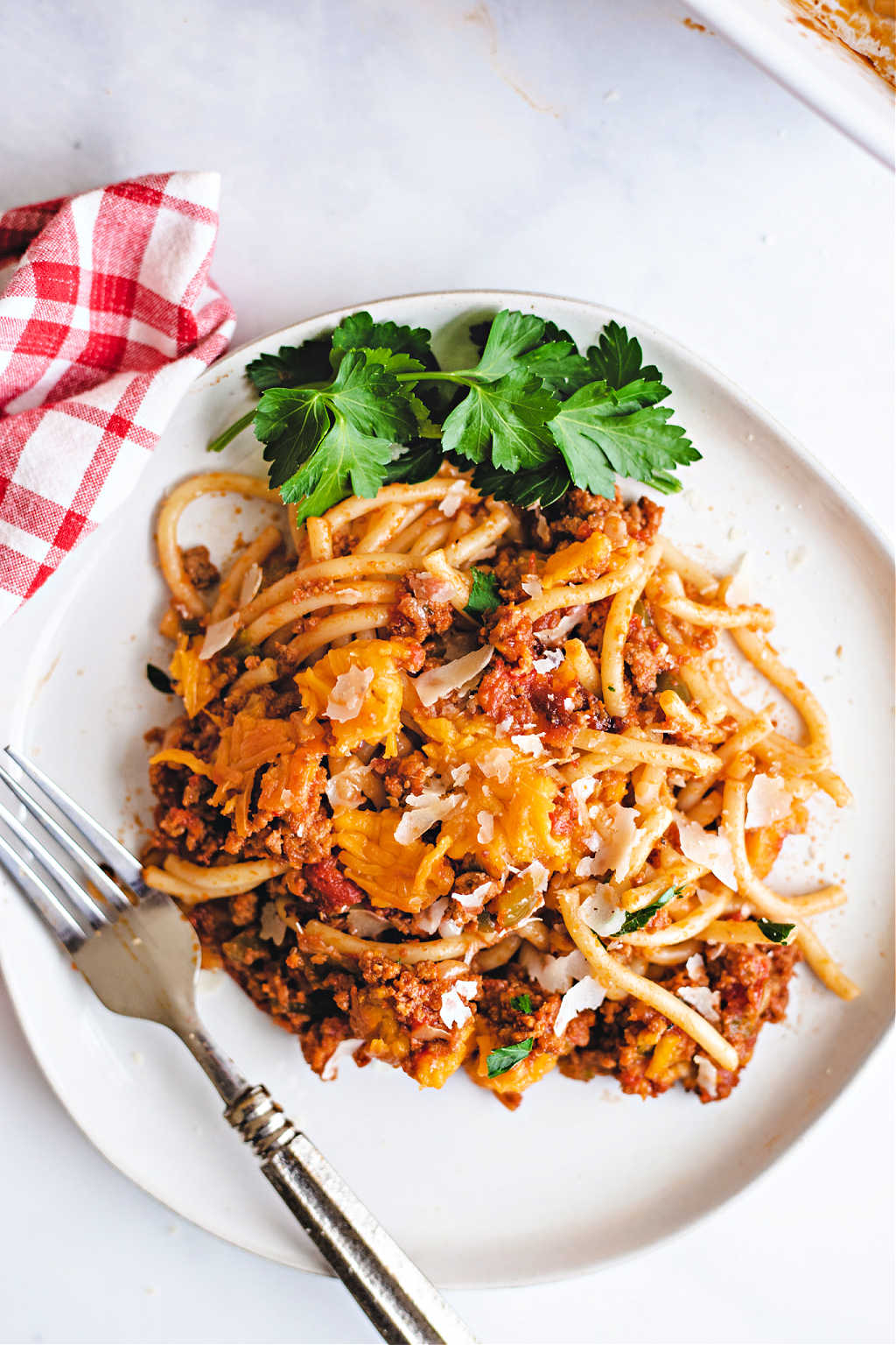 baked spaghetti on a white plate with a fork and red checkered napkin on a table.