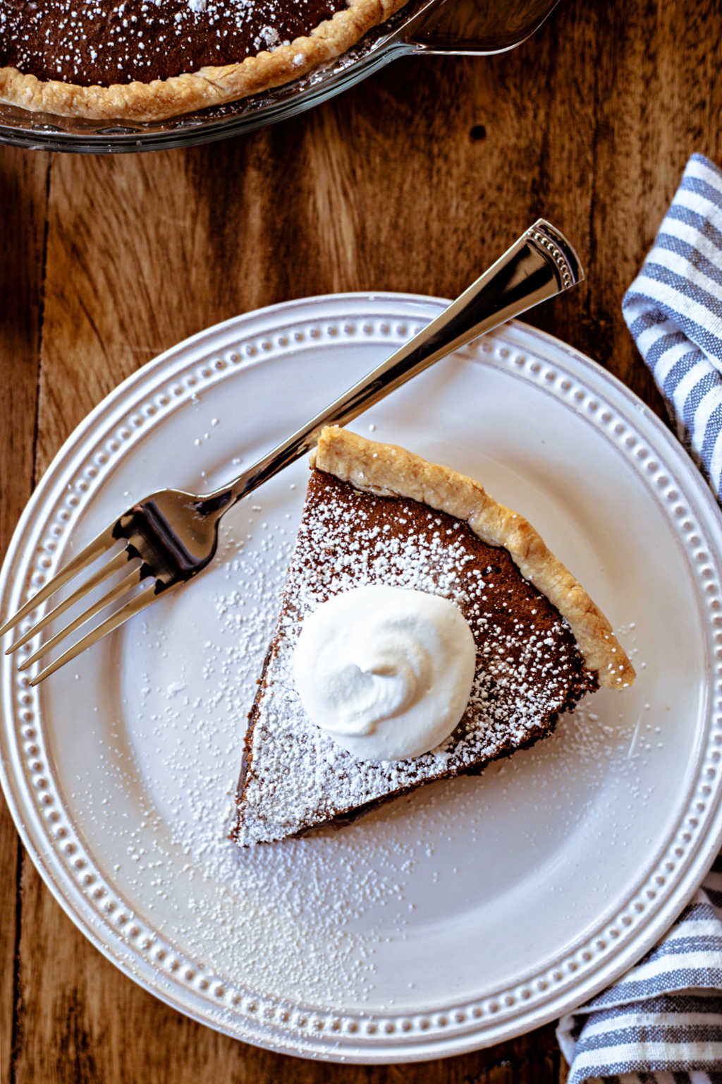 a slice of chocolate chess pie on a white plate on a wooden table.