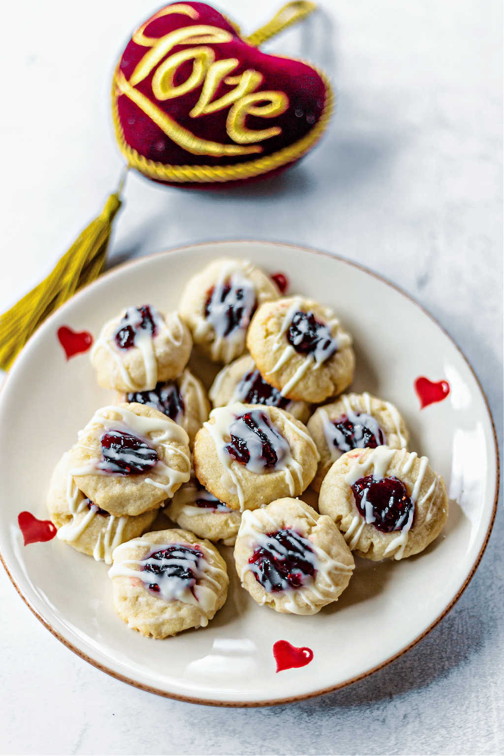 raspberry thumbprint cookies on a heart plate on a table