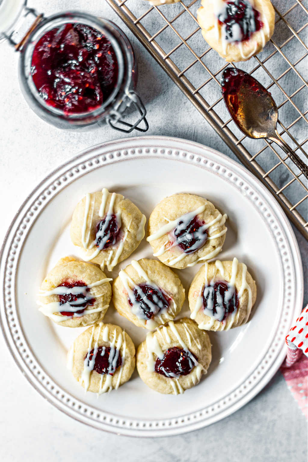lemon raspberry thumbprint cookies on a white plate with an open jar of raspberry jam on a table