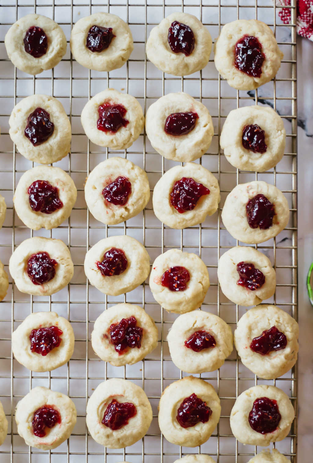 thumbprint cookies filled with raspberry jam on a wire cooling rack