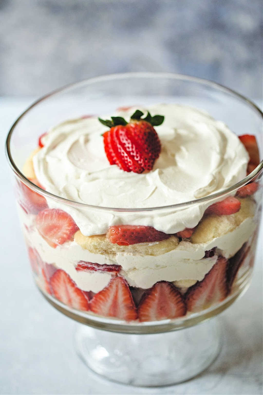 strawberry trifle with whipped cream and strawberry garnish on top in a glass trifle bowl.