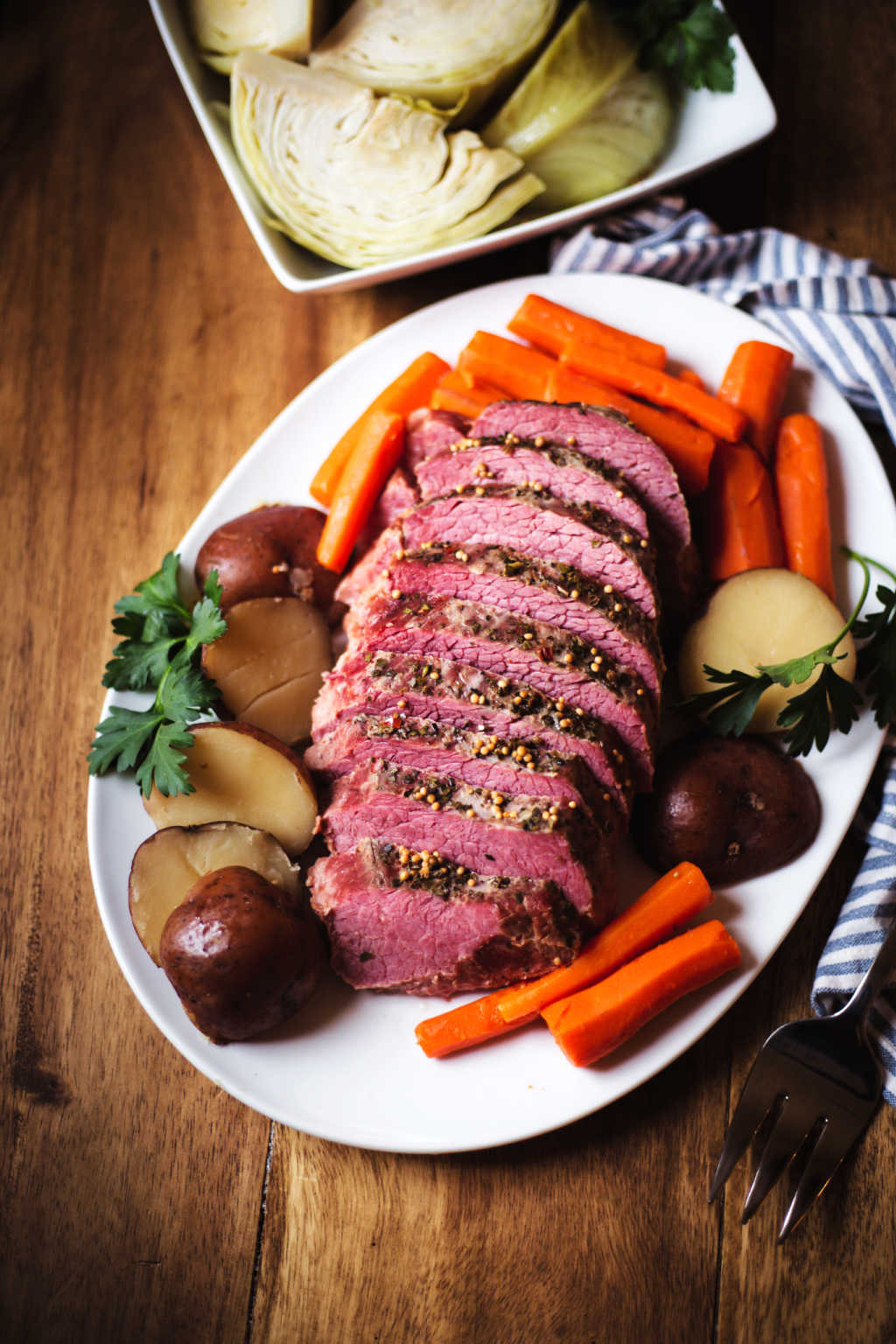 sliced slow cooker corned beef on a white platter with carrots and potatoes with a bowl of cabbage on a table.