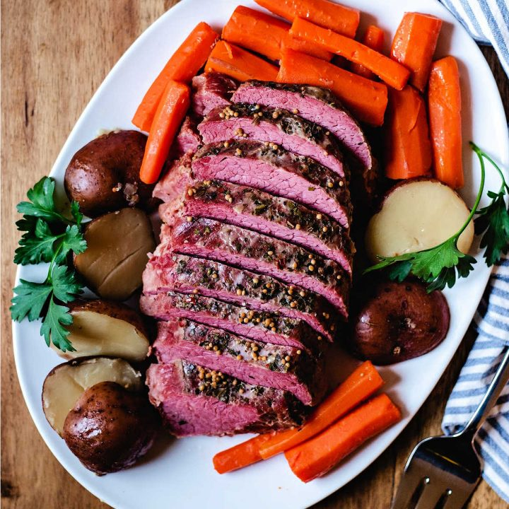 sliced slow cooker corned beef on a white platter with carrots and potatoes on a table.