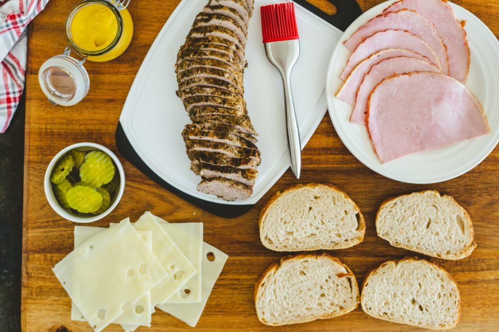 ingredients for Sandwich Cubano on a wooden table.
