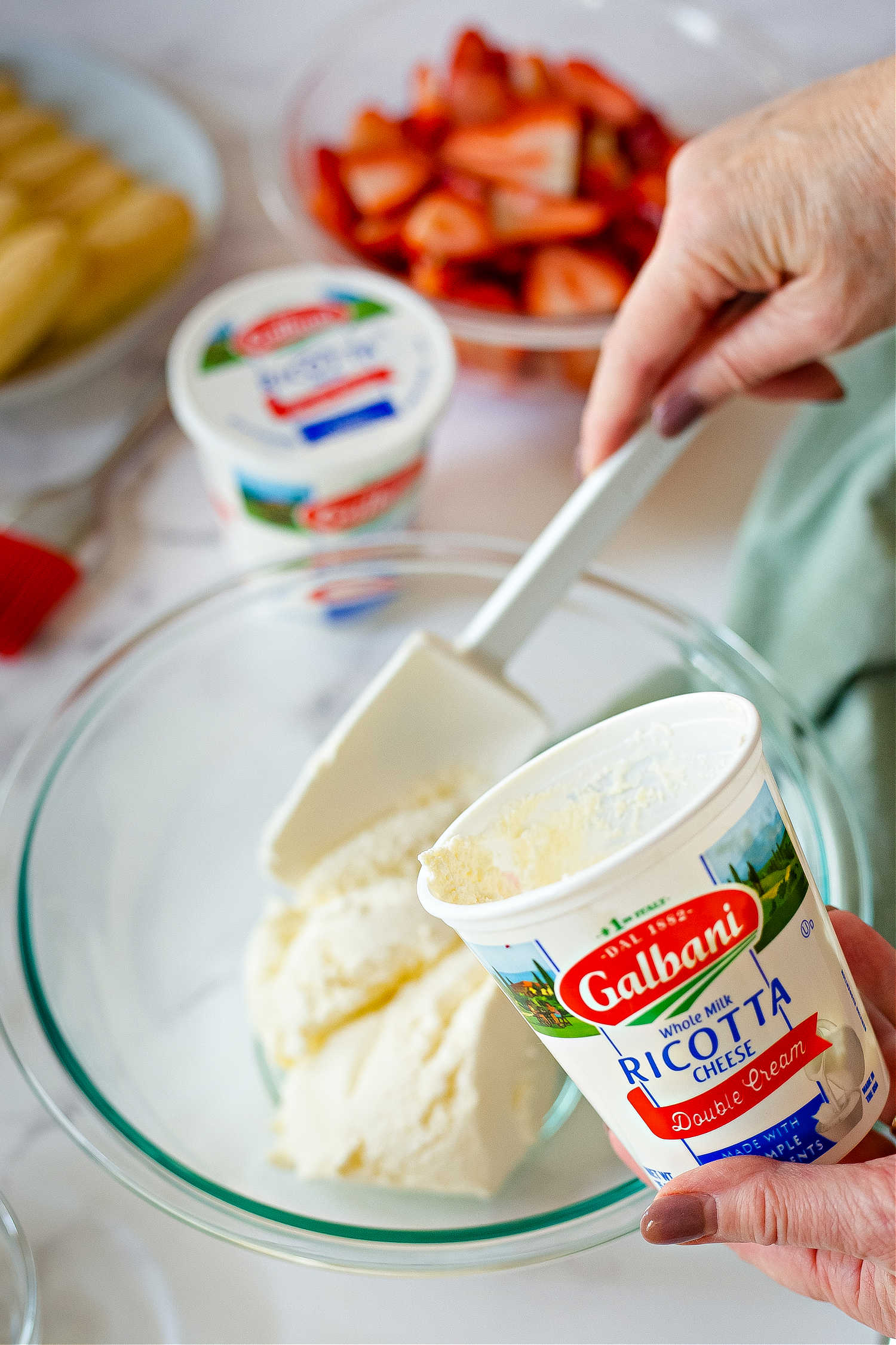 spooning ricotta cheese into a bowl for strawberry trifle.