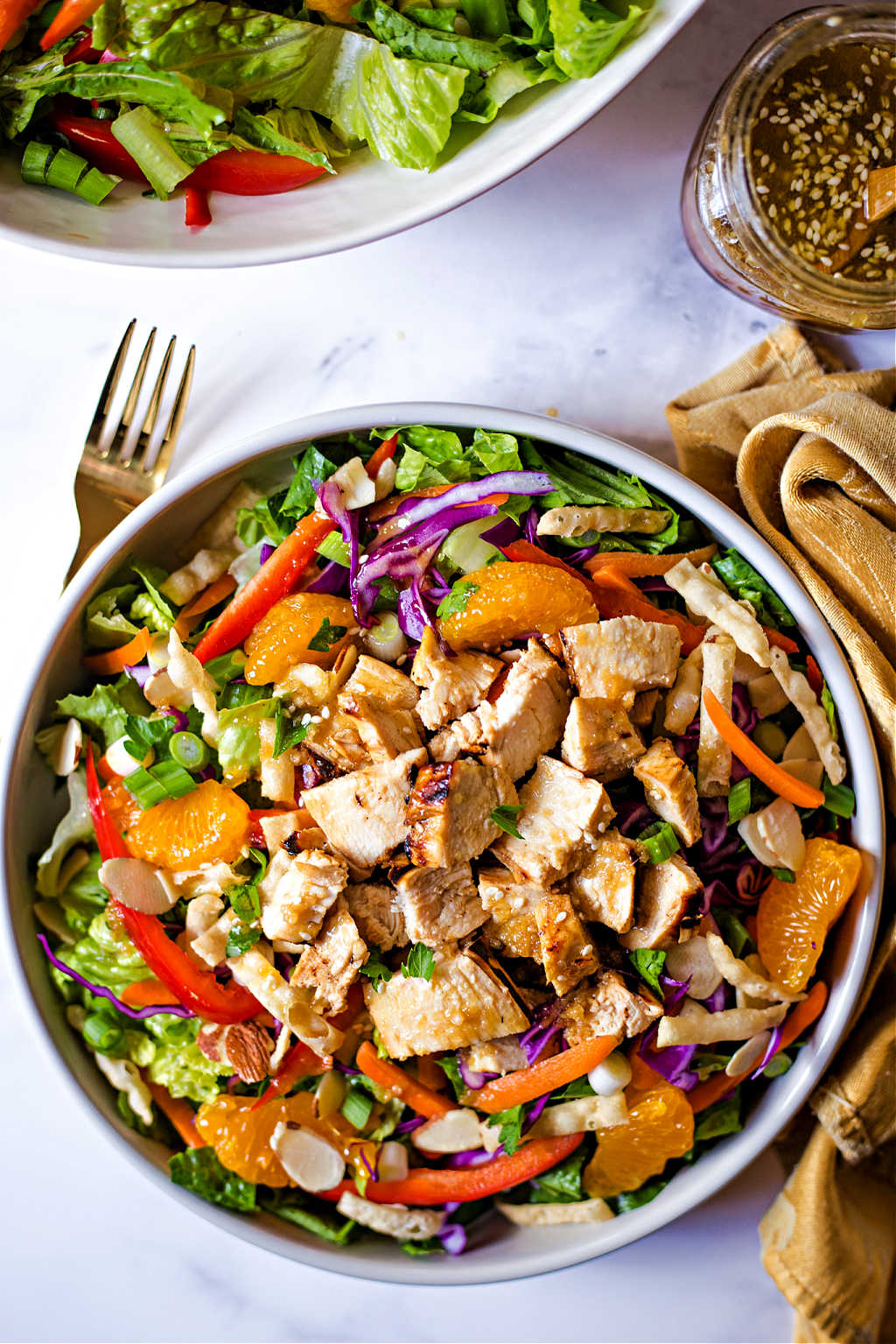 Asian Sesame Salad with Chicken in a bowl with a fork and jar of dressing on a table.