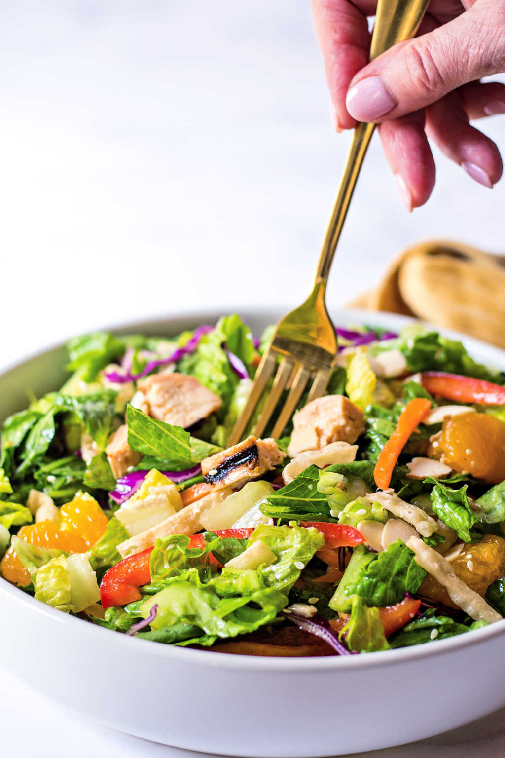 spearing a fork into a bowl of Asian Sesame Salad.