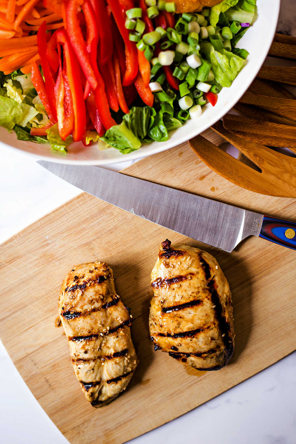 grilled chicken breasts on a cutting board for Asian Sesame Salad with Chicken.