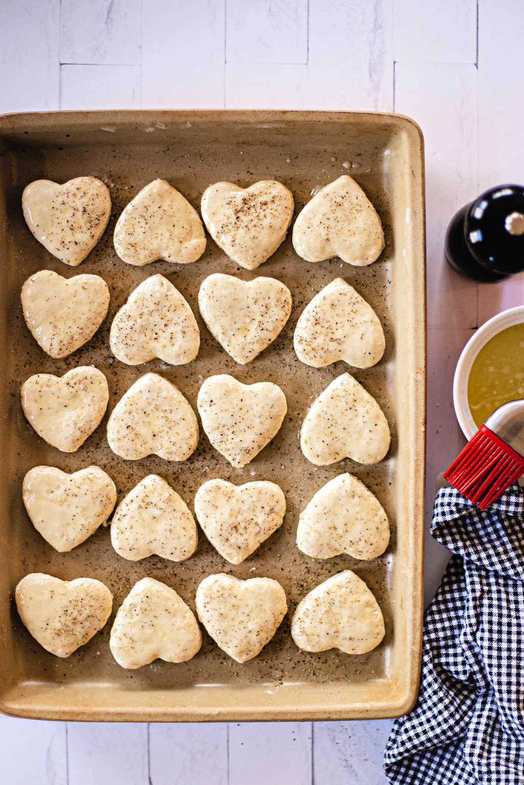 bread flour biscuits cut into heart shapes on a baking sheet.