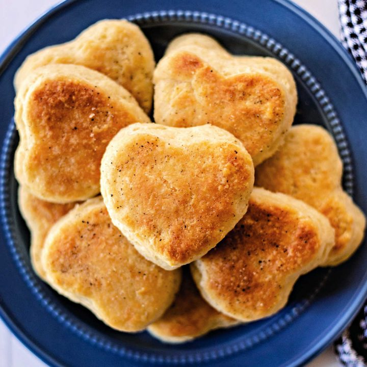 heart shaped bread flour biscuits stacked on a blue plate.