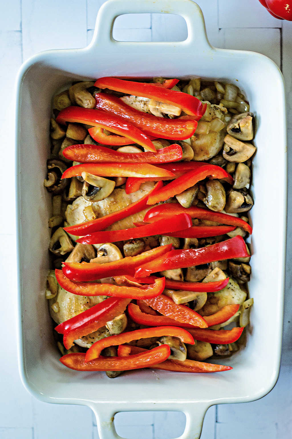 uncooked chicken breast with red bell peppers in a white baking dish on a table