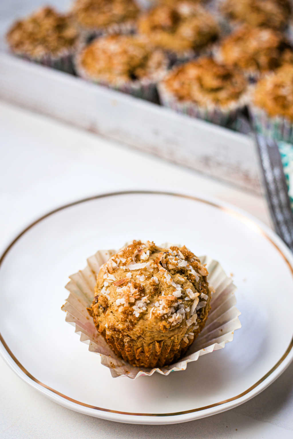 three chocolatey coconut banana muffins on a white plate on a table.