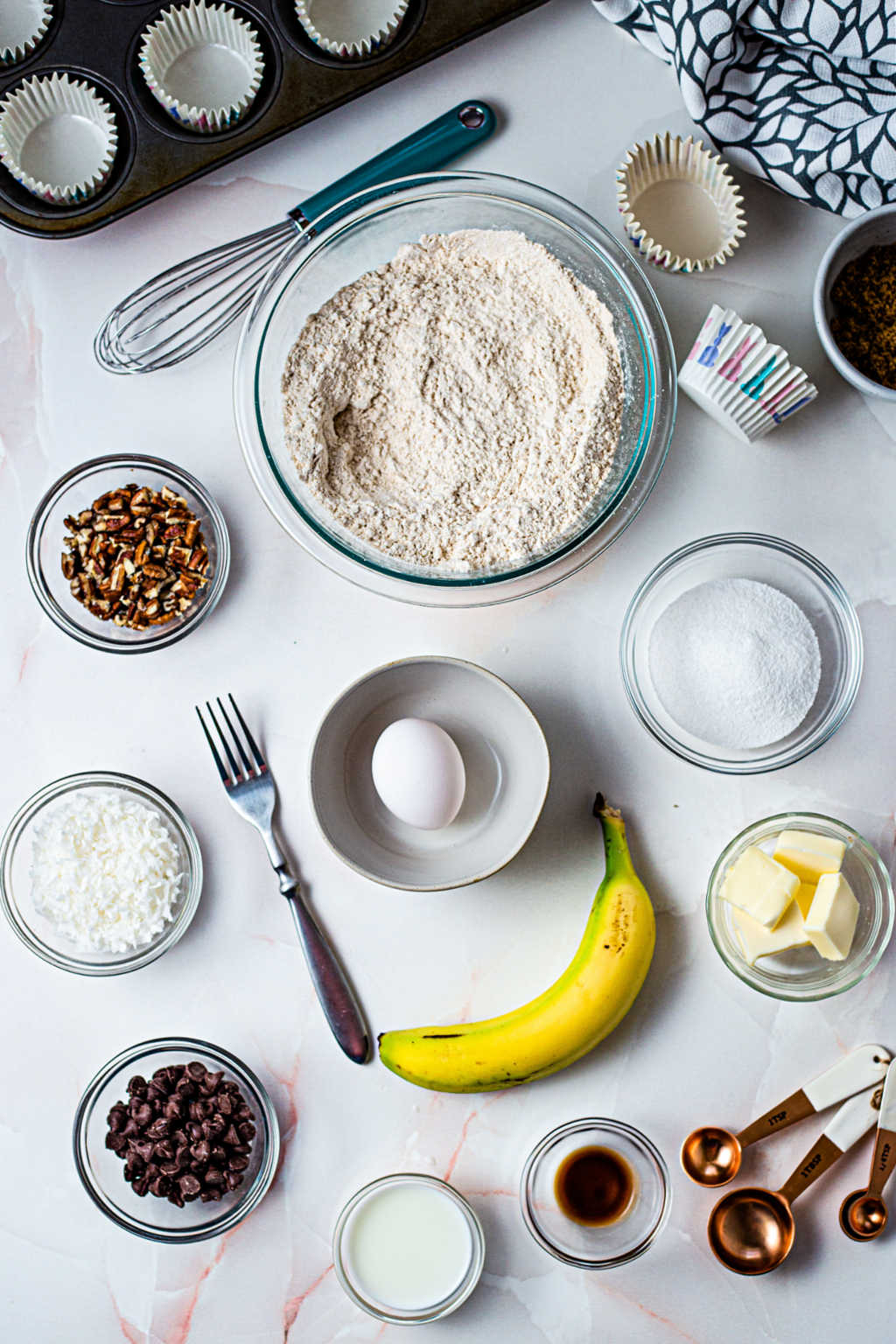 ingredients for three chocolatey coconut banana muffins on a table.