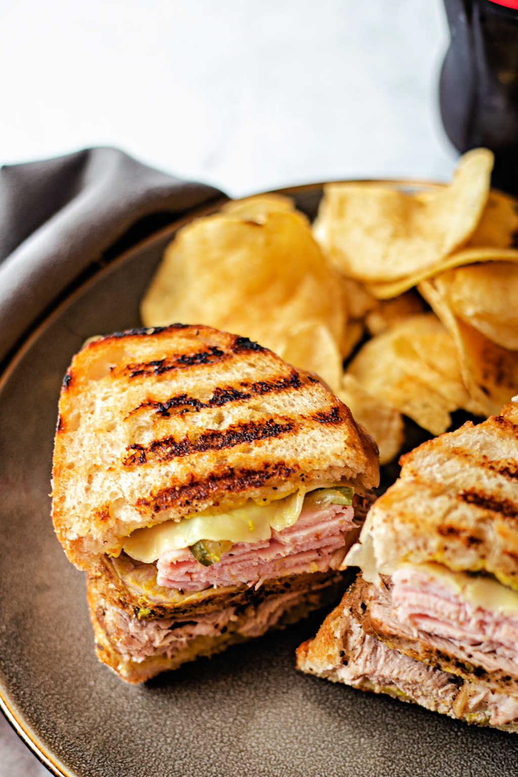 Sandwich Cubano on a plate with potato chips.