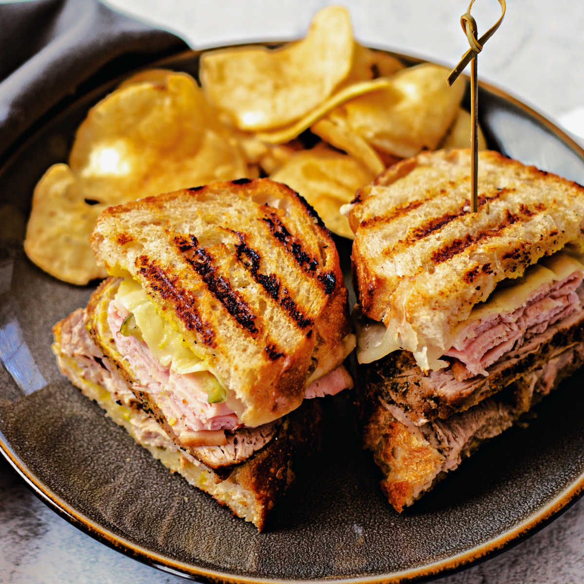 Sandwich Cubano on a gray plate with potato chips on the table.