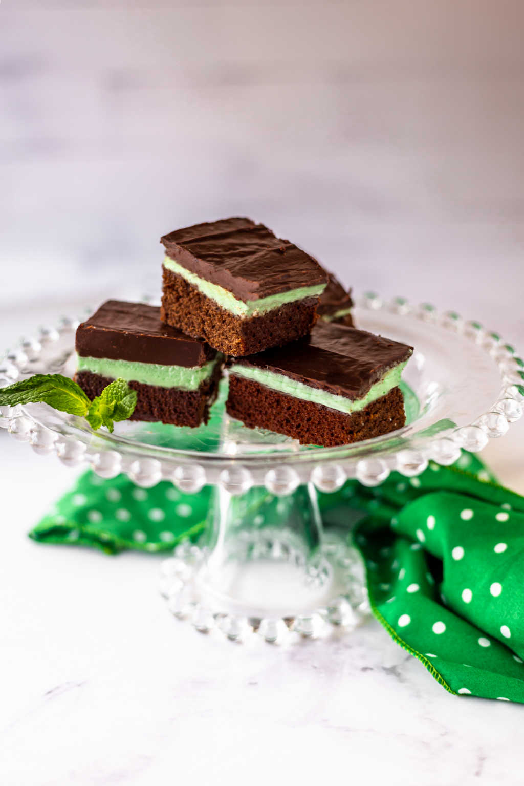 fudge mint brownies on a pedestal plate with a sprig of mint.