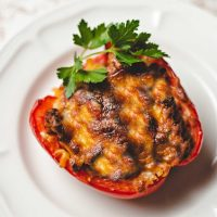 a keto stuffed red bell pepper on a white plate garnished with parsley on a kitchen counter.