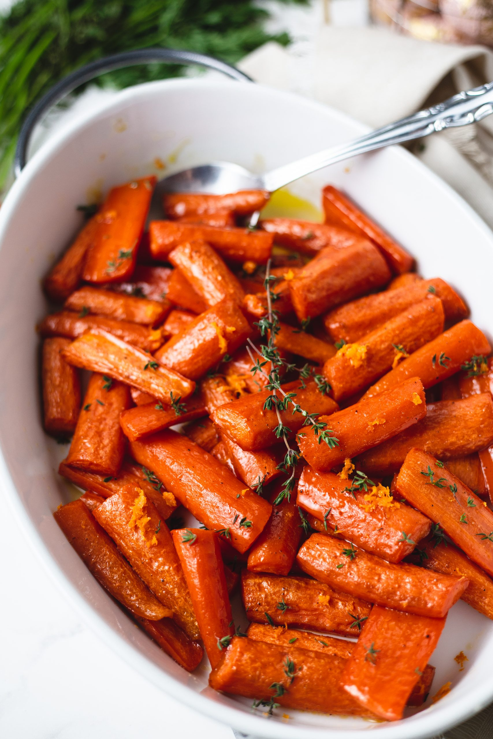 roasted carrots with honey in a white dish with a spoon.