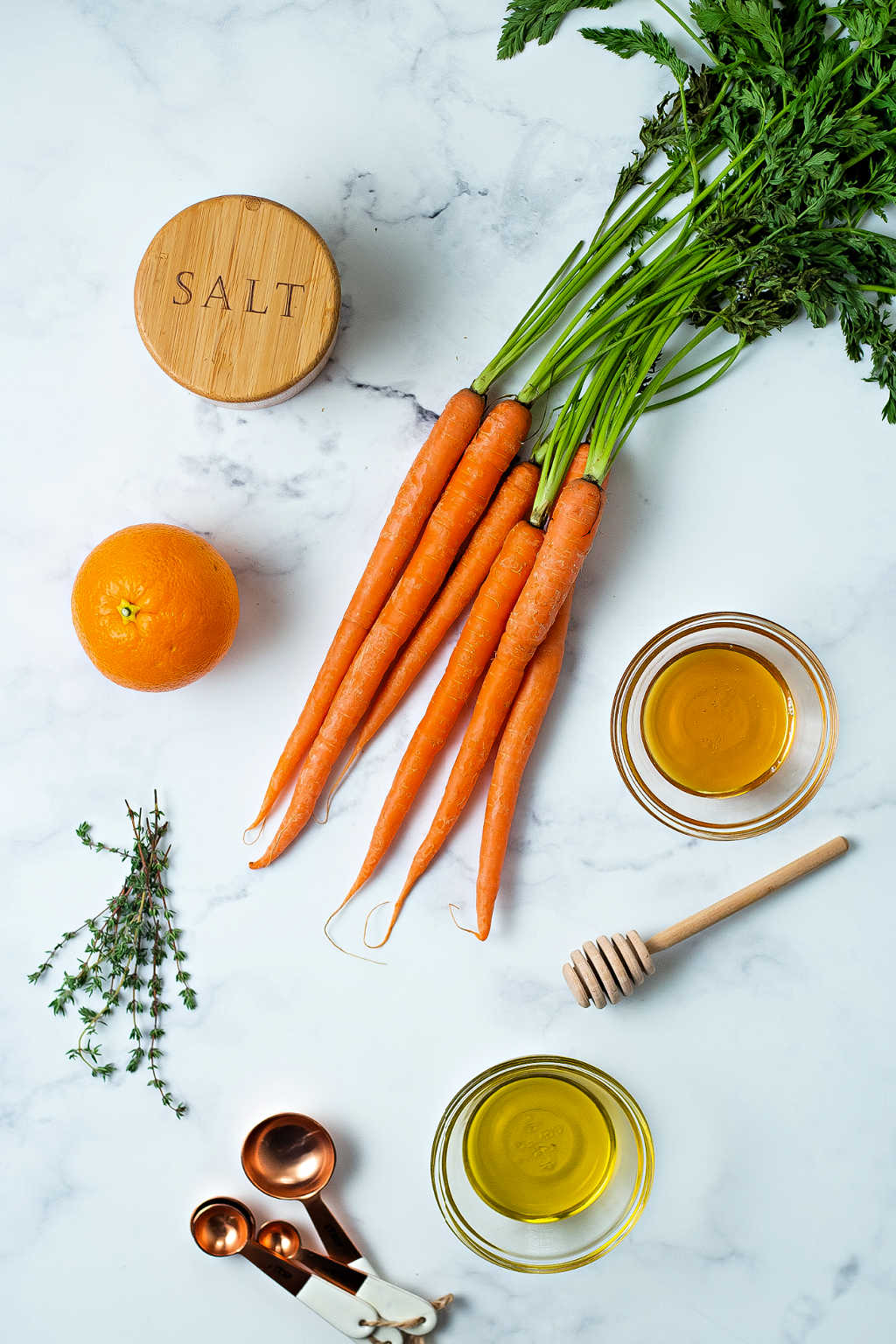 ingredients for roasted carrots with honey on a table.