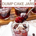 chocolate cherry dump cake in a jar with whipped cream and chocolate chips on a table.