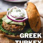 an open face Greek Turkey Burgers with Tzatziki Sauce on a wooden board.