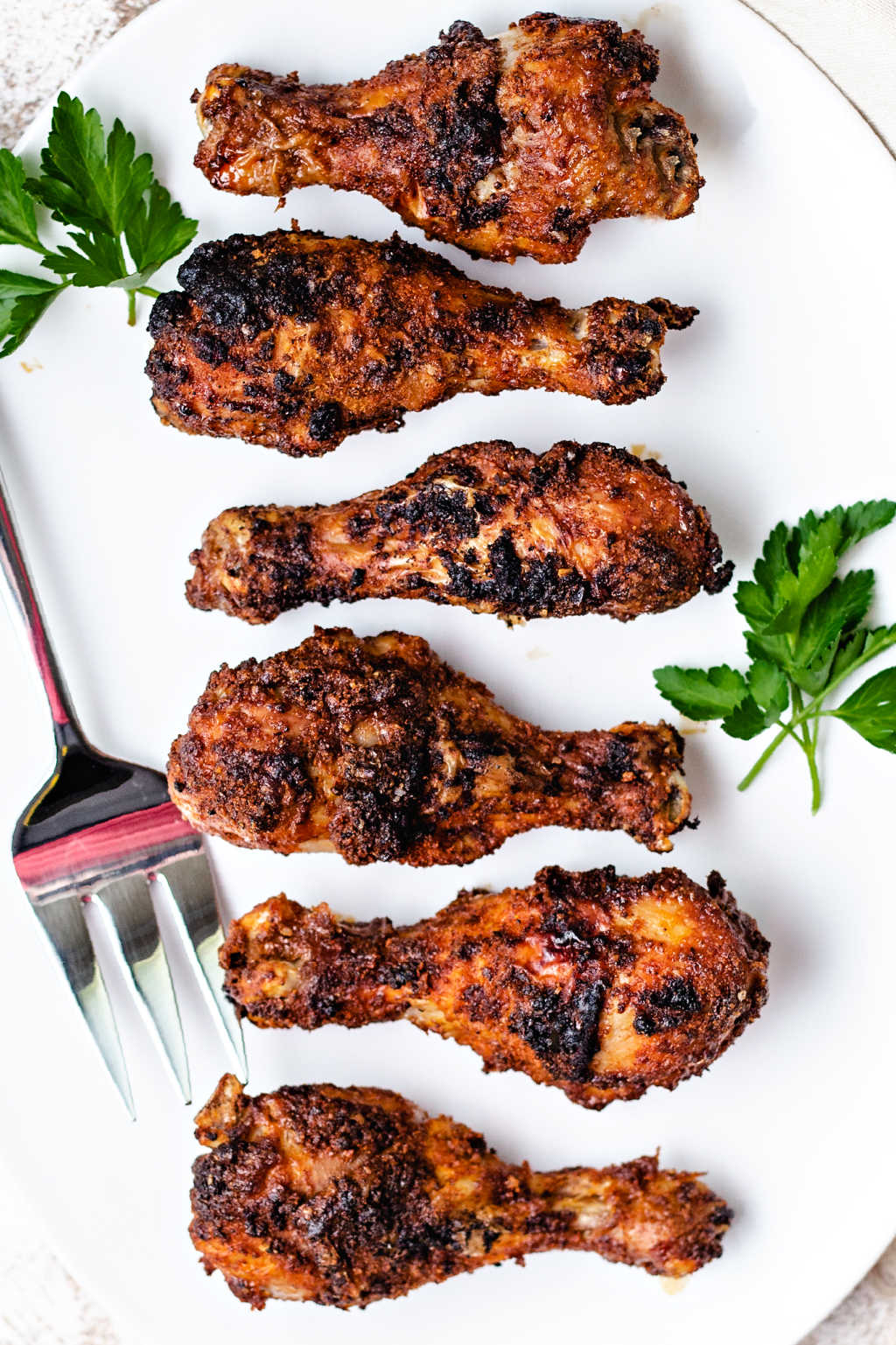 air fryer chicken legs on a white platter with parsley on a table.