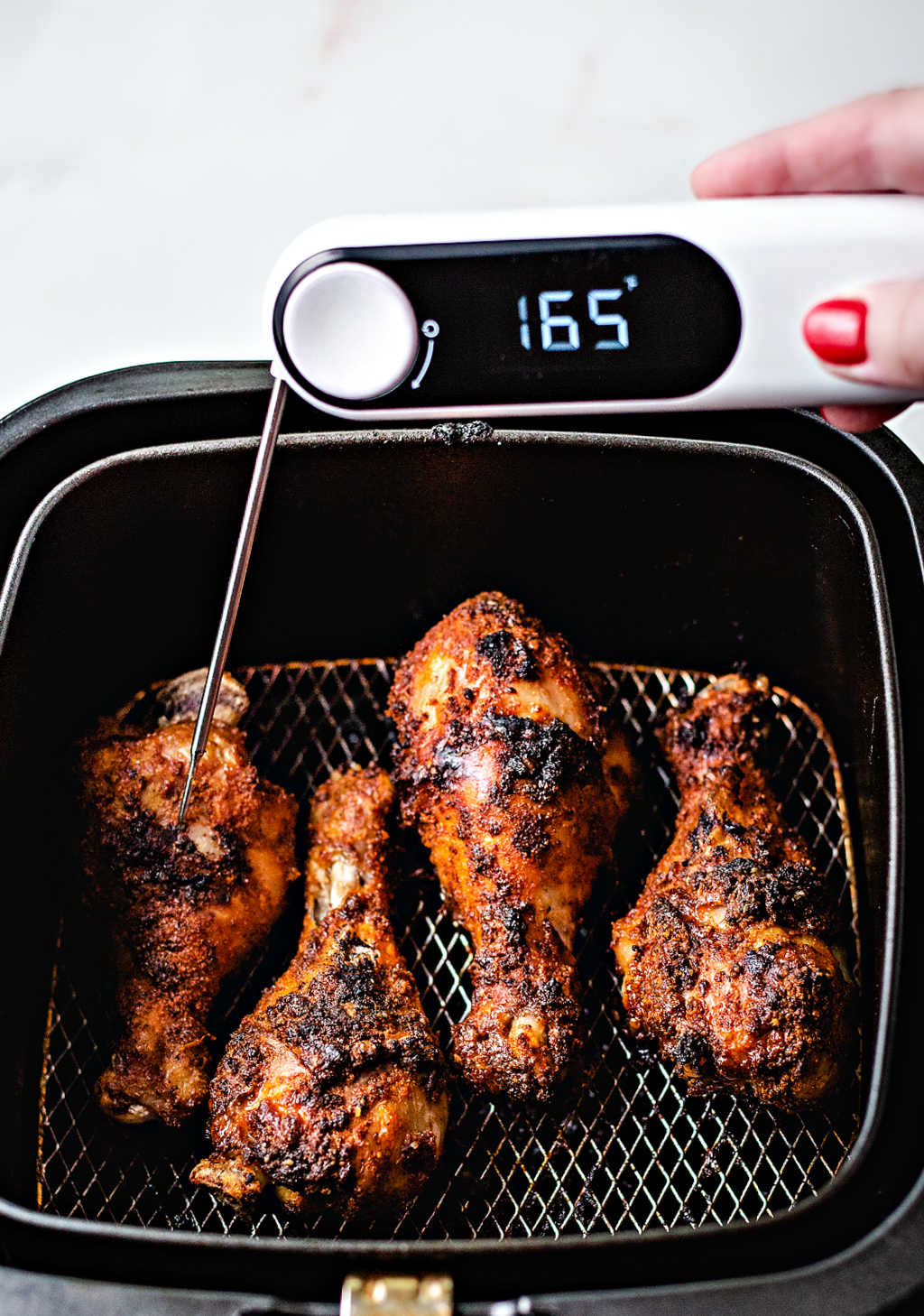 checking the internal temperature of air fryer chicken legs with an instant read digital thermometer.