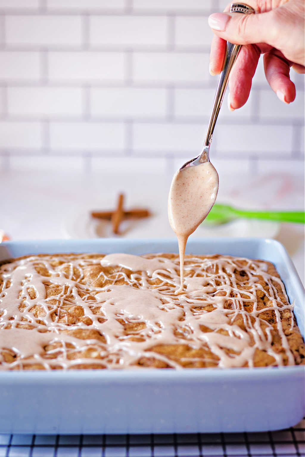 a spoon drizzling cinnamon glaze on a warm apple walnut snack cake.