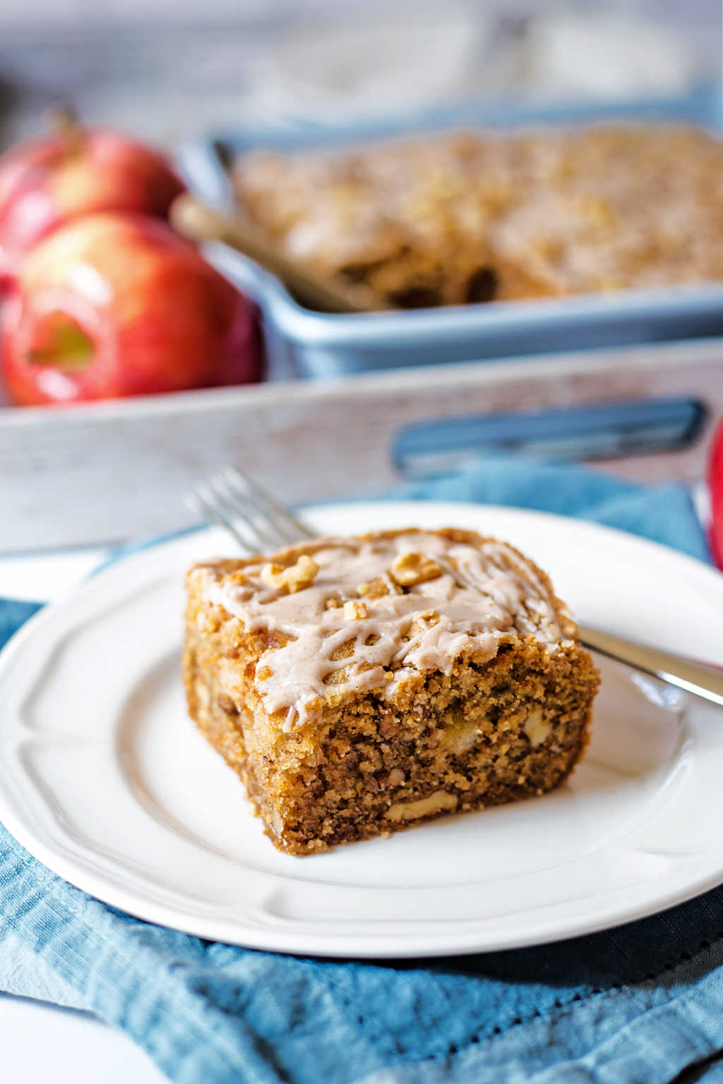 a slice of apple walnut cake on a white plate on a table with a tray of apples.