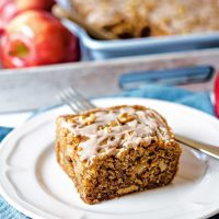 a slice of apple walnut cake on a white plate on a table.