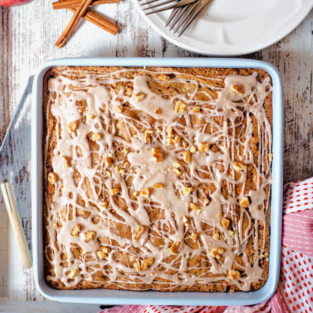 apple walnut cake in a baking pan on a table with a tray.