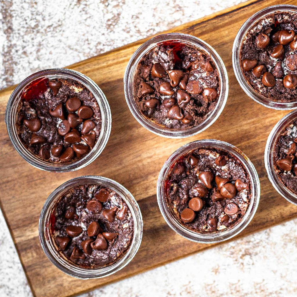 chocolate cherry dump cake in a jar on a wooden board on a table.
