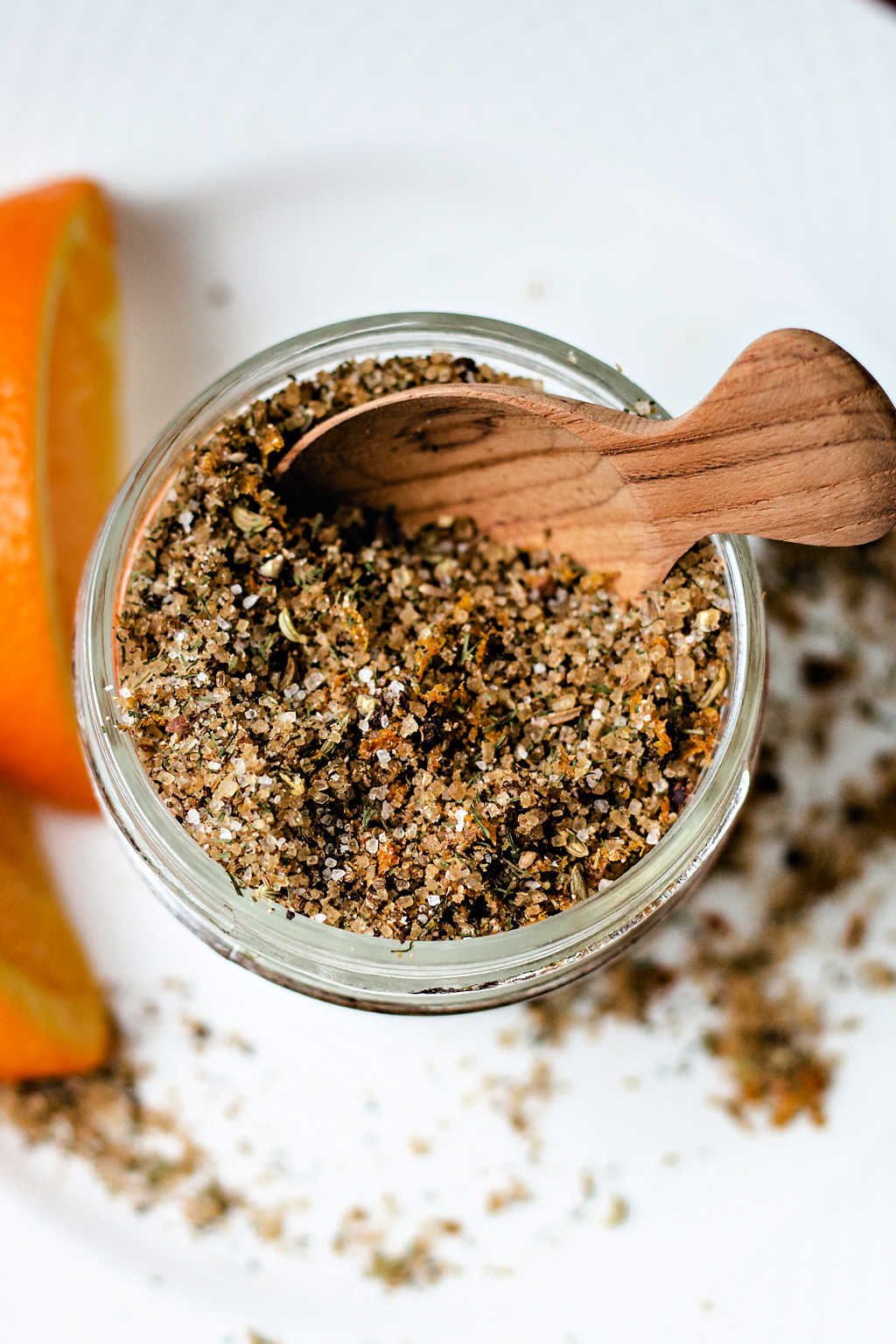 citrusy salmon rub in a small mason jar with a wooden spoon on a table.