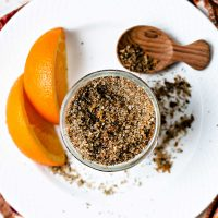 citrusy salmon rub in a glass jar on a white plate with orange wedges and a wooden spoon.
