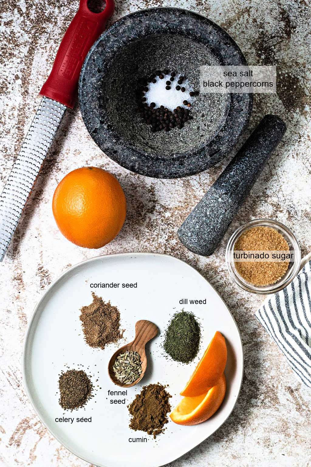 ingredients for salmon rub on a table with a mortar and pestle.
