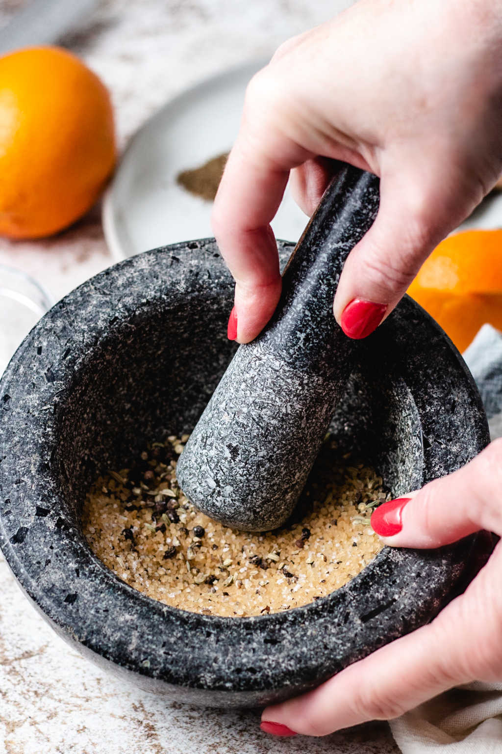 crushing spices with a pestle in a granite mortar for salmon rub.