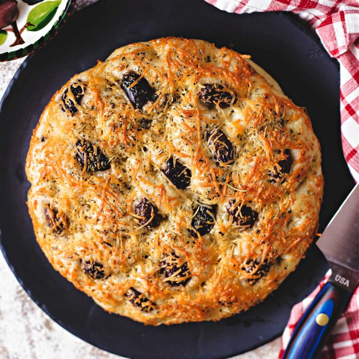 greek olive focaccia on a black stone platter with a carving knife.