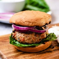 a greek turkey burger with red onion on a wooden board on a table.