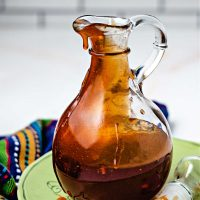 honey sriracha sauce in a glass decanter sitting on a green plate.