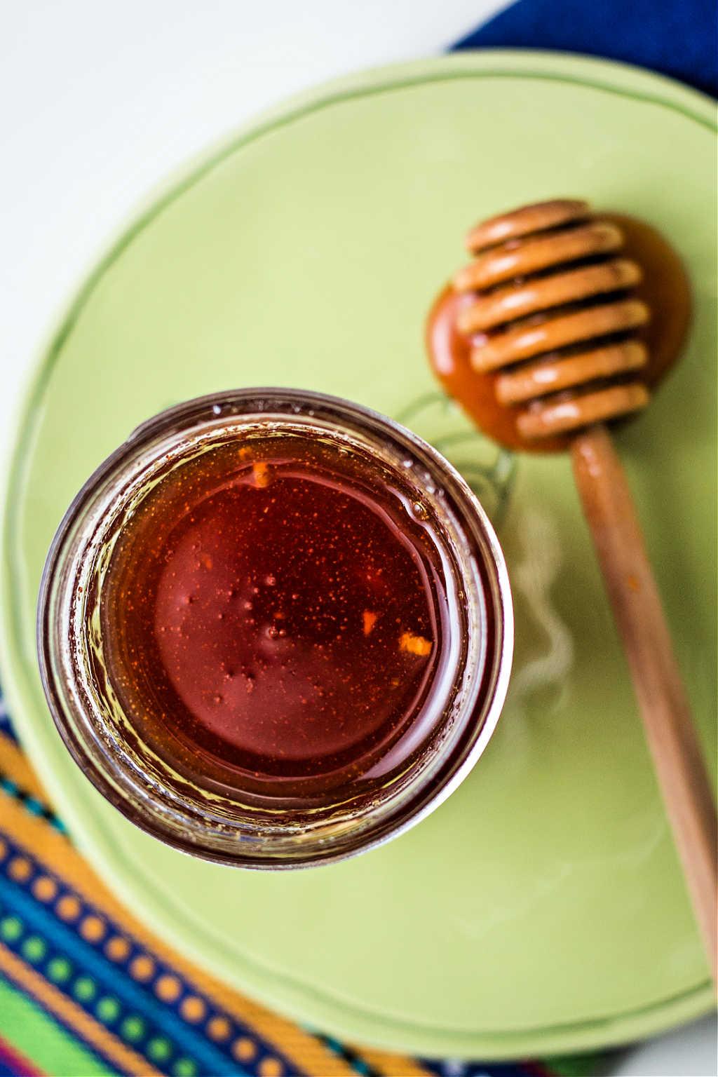 honey sriracha sauce in a jar on a table.