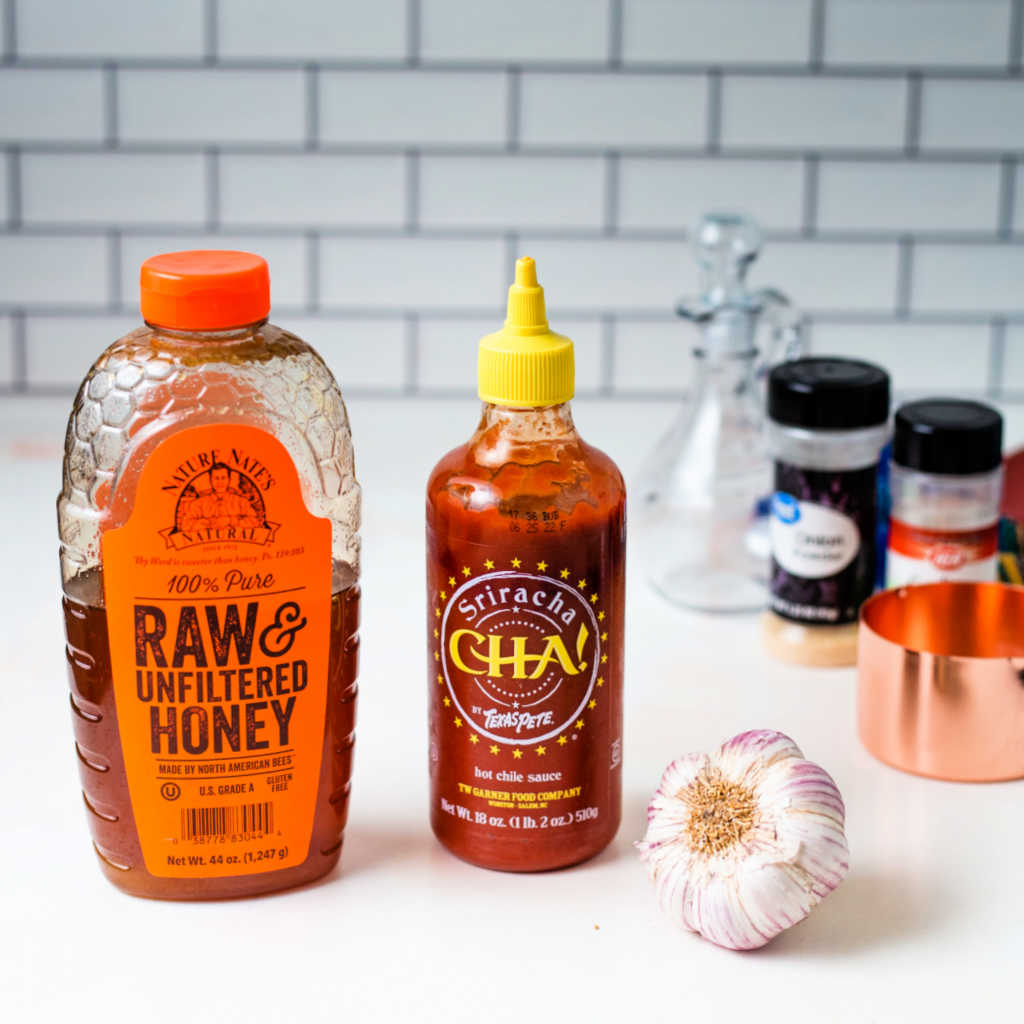 a bottle of honey, a bottle of sriracha, and a head of garlic on a kitchen counter.