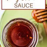honey sriracha sauce in a mason jar on a plate.