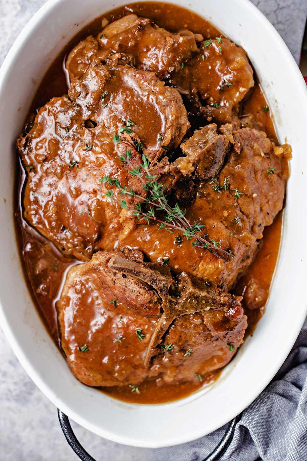 instant pot pork chops with apple gravy in an oval white serving dish.
