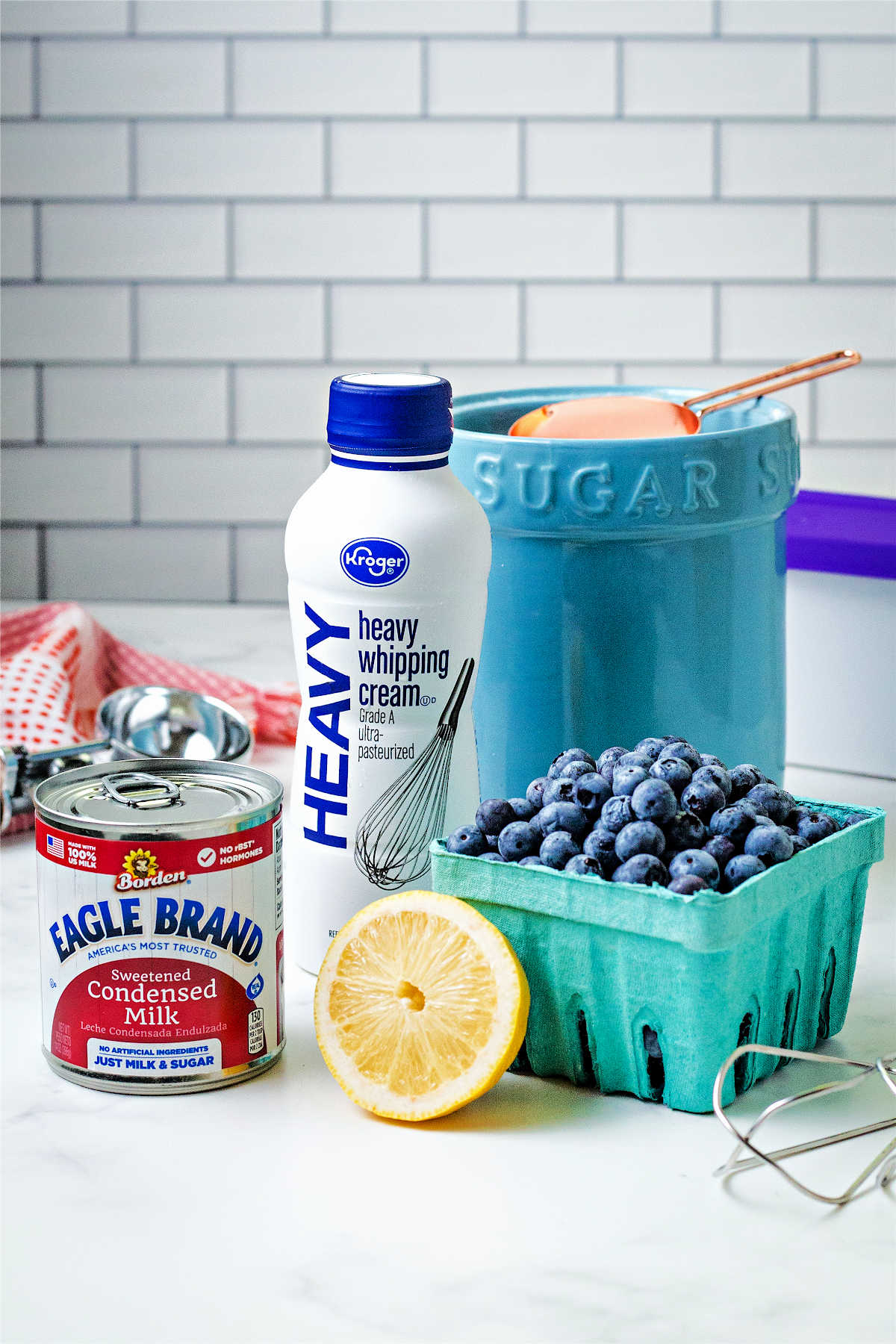 ingredients for blueberry ice cream on a counter: sweetened condensed milk, whipping cream, sugar, blueberries, and a lemon.