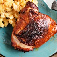 smoked chicken thigh on a blue plate with mac and cheese.