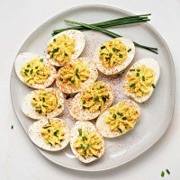a plate of southern deviled eggs on a table garnished with paprika and chives.