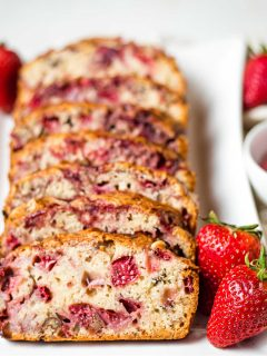 slices of strawberry bread on a white plate on a table.